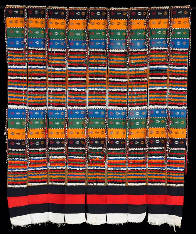 nine strips loosely tacked together; each strip has red, white and black striped ends, two sections of pile in white, black, red, green, orange and blue, two sections of black, orange, green and blue strips with geometric designs, bordered with two-colored twisted hanging braids, and central section of pile