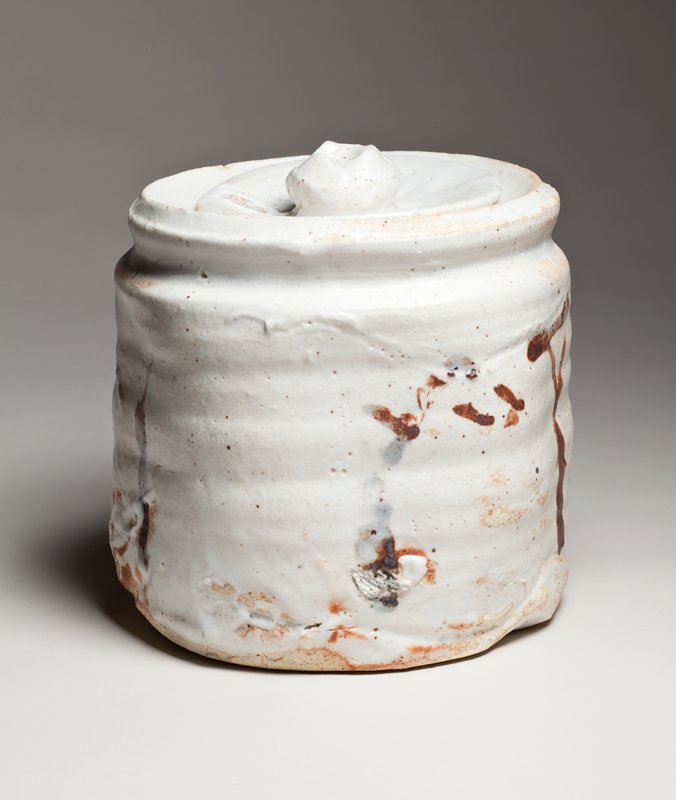 round, rough, white jar with rust colored markings; thick white glaze; horizontal ribbing on body; round, concave lid with globular handle
