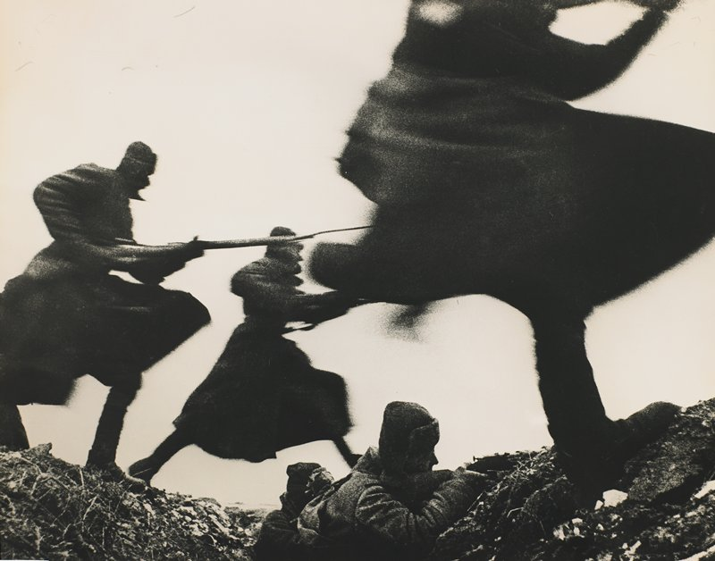 five men with guns, two in trench and three leaping over