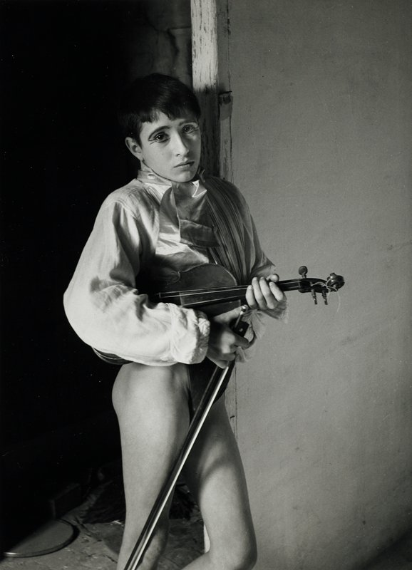 boy wearing eye makeup, silk tie and shirt with thick sleeves, holding a violin under his PR arm and a bow in his PR hand; bare legs