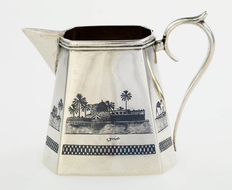 tapered octagonal body; pointed spout; decorated with palm trees, sailboats, camel with figure and village