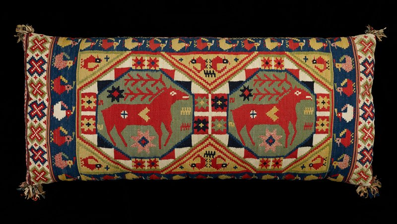 long pillow with tapestry woven cover; brightly colored with geometric designs, birds and deer on top; underside has bands of various colors and designs; fabric scrap pompons at corners