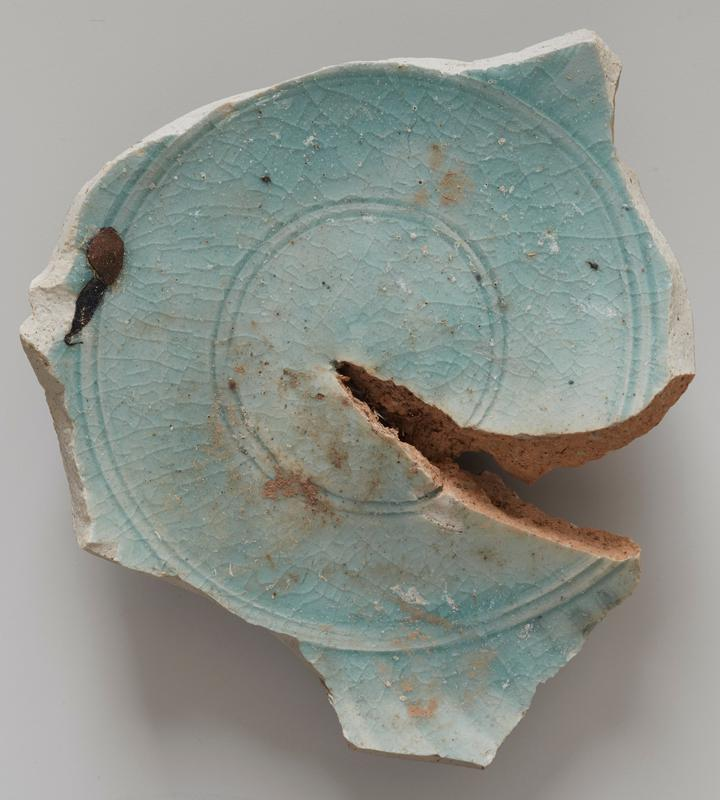 bottom of a ceramic vessel with ring foot; four concentric incised rings at center; green; .99 and .100 (fragments) may come from this vessel