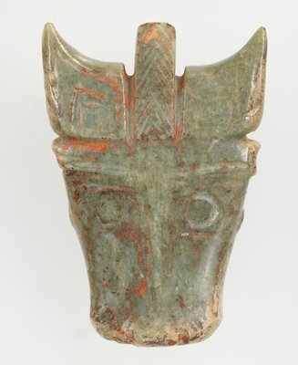 Mask of animal with horns can be identified as bull; simple incision to indicate the detail of the animal on the front only. Grey green jade; traces of red pigment and calcification