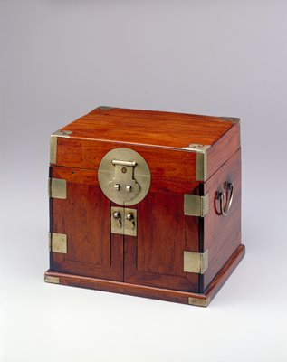 square seal chest; double front doors lock in place by flip lid; large circular latch and rectangular pulls, hinges and corner hardware made of silver; copper snowflake design inlaid to center of latch at top center front; handle at either side; two drawers above one longer at interior behind doors