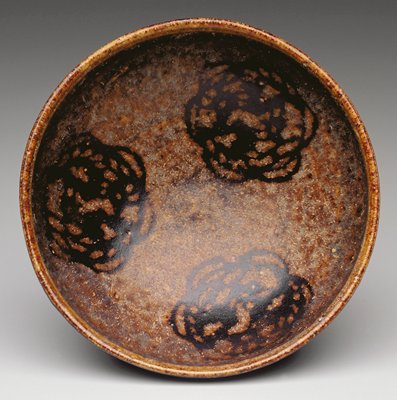 brown tones; conical form with lipped rim; interior decorated with three dark brown floral medallions; unglazed foot