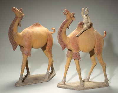 camel standing on diamond-shaped base; head up, tail up and curled; yellow with traces of red and black pigment; single hump