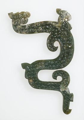 dark green jade; traces of claylike substance; Form of double S-shaped dragon in silhouette, ornamented with c-spiral grain pattern on surface and hooked spirals projecting from back of piece. Biconical perforation at lower arch of dragon.