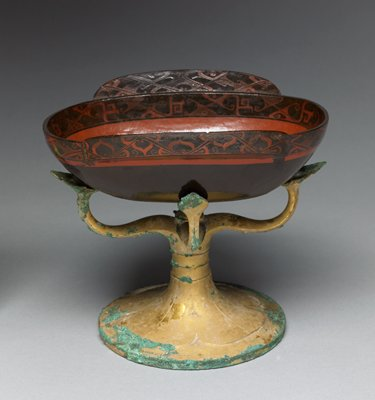 ovoid shape, with two handle-like protrusions on long sides; rust-red and brown; rim and handles painted with running geometric designs